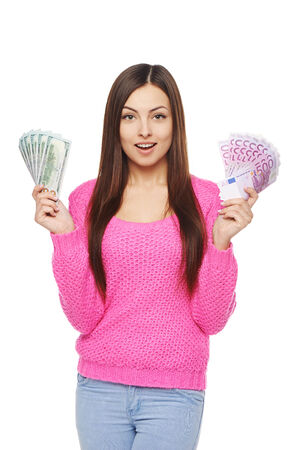 one people: Surprised young woman in bright pink sweater holding us dollar money in one hand and euro cash money in another hand, over white background