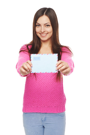 outstretching: Good news concept. Happy woman in pink sweater giving you blank air mail envelope, over white background. Focus at girl.
