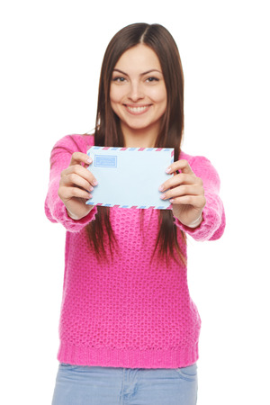 Good news concept. Happy woman in pink sweater giving you blank air mail envelope, over white background. Shallow depth of field, Focus at envelope. photo