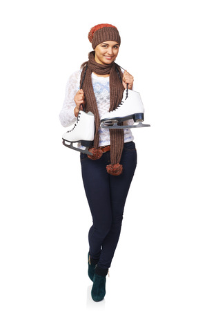 iceskates: Full length of smiling young woman wearing warm hat and scarf carrying a pair of ice skates, over white background