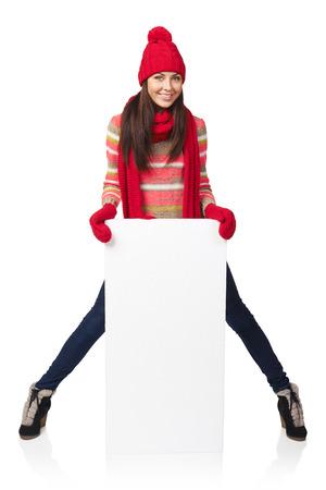 outerwear: Donna felice esterno in inverno in piedi in piena lunghezza appoggiata sul banner bianco in studio su sfondo bianco