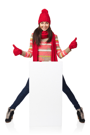 outerwear: Happy woman in winter outerwear standing in full length leaning on white banner and gesturing thumb up sign, at studio over white background