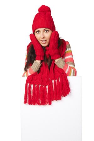 outerwear: Donna sorpresa esterno in inverno in piedi dietro striscione bianco in studio su sfondo bianco Archivio Fotografico