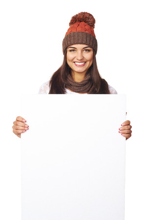 Smiling happy woman in winter hat peeking out of the edge of white banner over white studio background photo