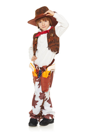 uplifting: Full length of little boy in a suit of the cowboy welcoming uplifting his hat, on a white background