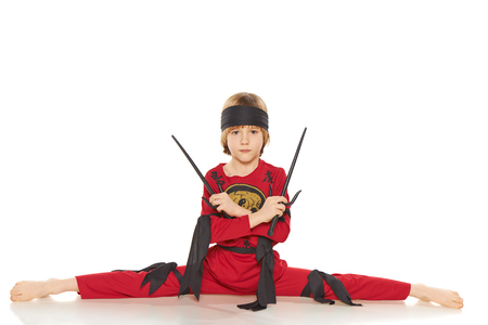 sabre's: Young Ninja doing the splits and holding sabres over white background