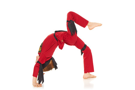 boy gymnast: Young Ninja showing acrobatic trick, over white background