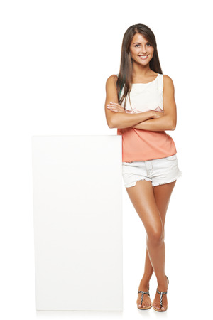 board shorts: Full length of beautiful tanned woman in shorts standing leaning on white blank advertising board banner, over white background