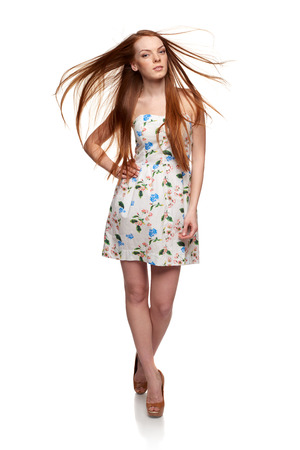 Full length of redhead woman in summer floral dress walking with hair flying over white background