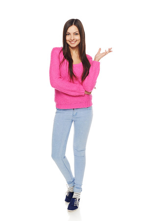 Full length happy young female in blue jeans and pink sweater showing open hand palm with copy space for product or text
