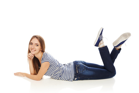lying on side: Profile of smiling beautiful woman lying on the floor over white background and looking at camera Stock Photo