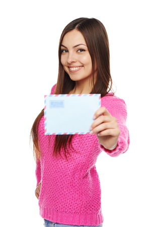 News concept. Happy woman in pink sweater giving you blank air mail envelope, over white background. Focus at girl. photo
