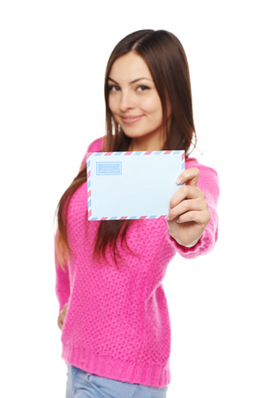 outstretching: News concept. Happy woman in pink sweater giving you blank air mail envelope, over white background. Shallow depth of field, Focus at envelope. Stock Photo