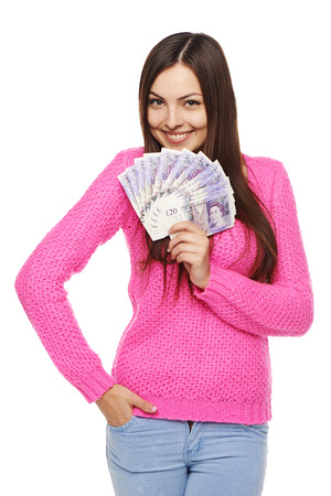 woman holding money: Closeup of young beautiful woman with British pounds in hand