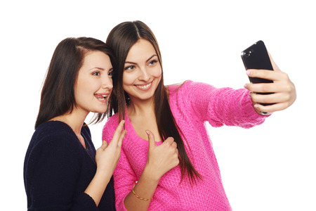 Two girls friends taking selfie with smartphone, isolated on white background photo