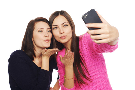 Two girls friends taking selfie with smartphone, blowing a kiss in the camera, isolated on white background