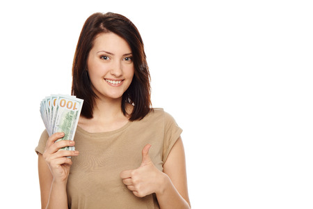 Closeup of young beautiful woman with us dollar money in hand, gesturing thumb up, over white background, with copy spac Imagens