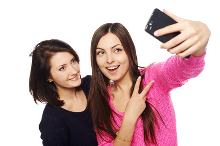 taking: Two girls friends taking selfie with smartphone, isolated on white background