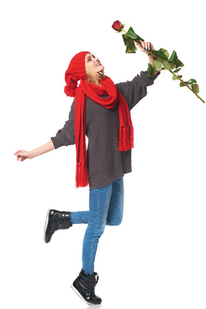 Full length portrait of joyful youngwoman with red rose dancing of happiness, over white background photo