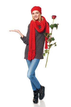 space for copy: Full length portrait of young beautiful woman holding red rose and showing open hand palm with copy space for product or text, over white background
