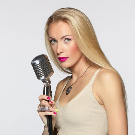 Elegant blond female with silver microphone looking at camera