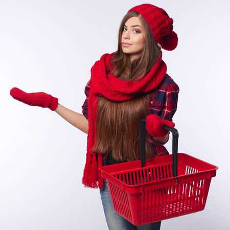 Winter shopping concept. Smiling beautiful woman in winter red hat and muffler holding empty shopping basket and showing open palm blank copy space over gray background