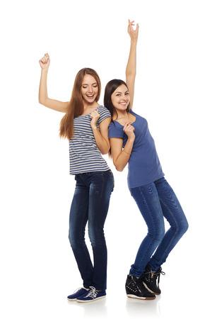 fondo blanco: Dos de las niñas feliz jóvenes amigos bailando de alegría en toda su longitud, aisladas sobre fondo blanco