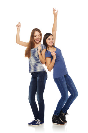 Two happy young girls friends dancing of joy in full length, isolated on white background Imagens
