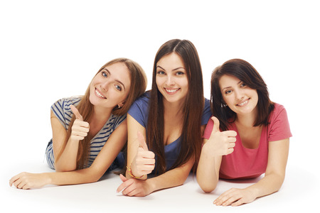 female friends: Front view of girls friends lying smiling on floor looking at camera and gesturing thumbs up, over white background Stock Photo