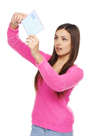 guess: Woman looking at envelope trying to guess what is in it, over white background Stock Photo