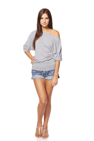 hands on hip: Full length of young slim tanned female in denim shorts standing with hand on hip, isolated on white background Stock Photo