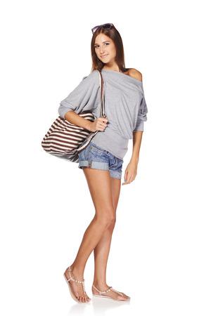 sandalia: Longitud total de sonriente joven delgada mujer curtida en pantalones cortos de mezclilla con mochila y gafas de sol, aislado en fondo blanco