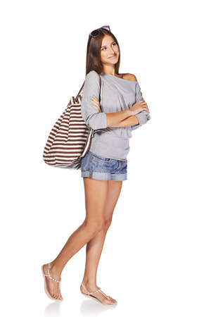 Full length of smiling young slim tanned female in denim shorts with backpack and sunglasses looking away at blank copy space, isolated on white background photo