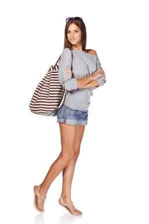 バックパック、サングラス、白い背景で隔離のデニムのショート パンツで笑顔若いスリム日焼けした女性の完全な長さ