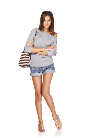 Full length of smiling young slim tanned female in denim shorts with backpack and sunglasses, isolated on white background photo