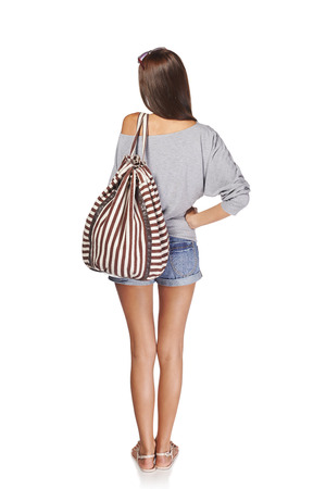 woman standing back: Back view Full length of young slim tanned female in denim shorts with backpack, isolated on white background Stock Photo