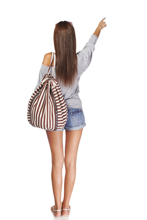 Back view Full length of young slim tanned female in denim shorts with backpack pointing at blank copy space, isolated on white background Stock Photo