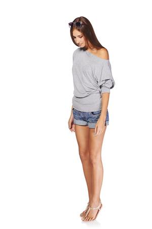 Volledige lengte van jonge stijlvolle slanke gebruinde vrouw in denim shorts staan kijken neer op lege kopie ruimte aan haar voeten, op een witte achtergrond