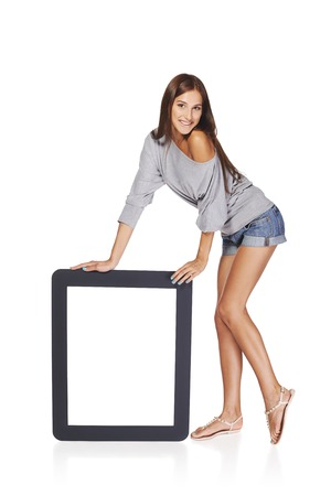 Full length of playful woman showing blank empty screen with copy space. Happy caucasian girl standing leaning at tablet frame over white background