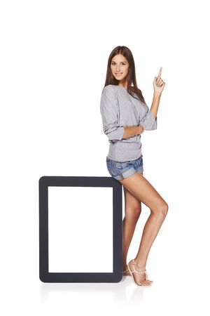 Full length woman showing blank empty screen with copy space. Happy caucasian girl standing with tablet frame and pointing finger up, over white background Stock Photo