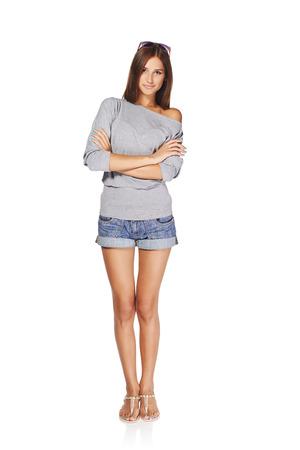 デニムのショート パンツが白い背景で隔離の折られた手で立っている若いスタイリッシュなスリムな日焼けした女性の完全な長さ