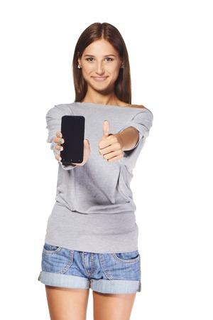 Giovane donna che mostra mobile cellulare con schermo in bianco e gesticolando pollice alto, su sfondo bianco. Profondità di campo, messa a fuoco al telefono. Archivio Fotografico - 36465017