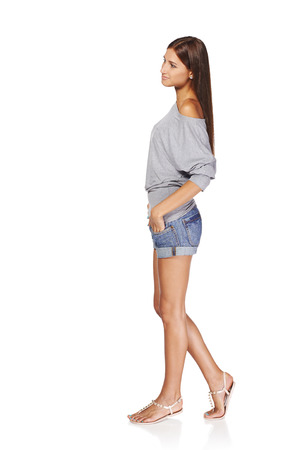 Full length side view of relaxed young stylish slim tanned female in denim shorts looking forward, isolated on white background