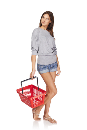 spending full: Shopping woman. Full length casual young woman standing with empty shopping cart basket and looking away at blank copy space, over white background