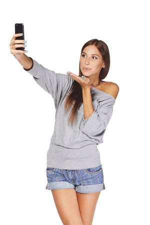 beautiful teen girl: Happy flirting young girl taking pictures of herself at smart phone blowing a kiss, over white