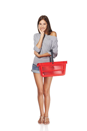 spending full: Shopping woman. Full length casual young woman standing smiling with empty shopping cart basket, over white