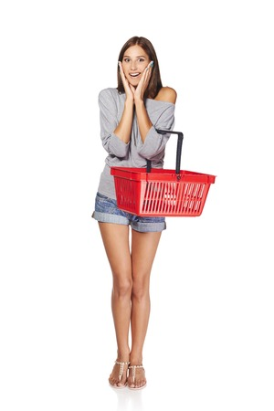 Shopping woman. Full length of surprised casual young woman standing with empty shopping cart basket holding her head in amazement and opened mouth, over white  Stock Photo