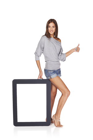 Full length woman showing blank empty screen with copy space. Happy caucasian girl standing with tablet frame and gesturing thumb up sign, over white