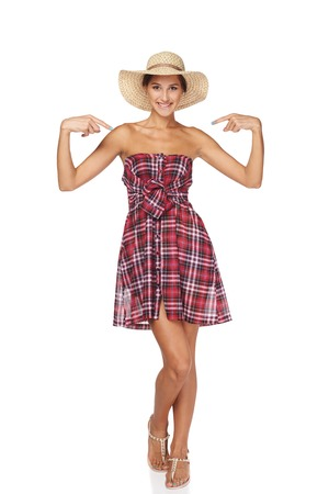 egocentric: Full length portrait of happy playful woman in country style pointing at herself, isolated on white  backgorund.  Smiling woman wearing chequered summer dress and broad-brim straw hat.