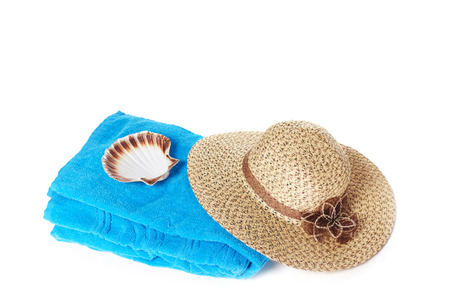 towelling: Blue beach towel with broad-brim straw summer hat and sea shell, isolated on white background